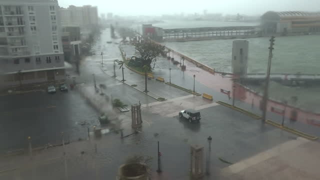 Shows exterior shots police vehicles driving along wet roads as strong winds blow and rain falls as Hurricane Maria hits Puerto Rico Hurricane Maria...