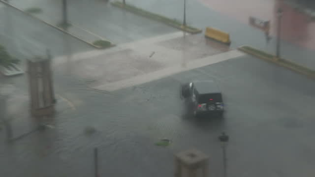 Shows exterior shots police vehicles driving in wind and rain along flooded street round bay in San Juan after worst of Hurricane Maria has passed...