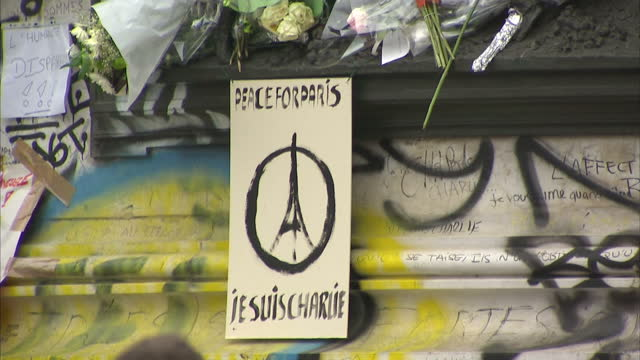 stockvideo's en b-roll-footage met shows exterior shots posters tributes and graffiti for victims of the paris terror attacks added to the monument in the centre of the place de la... - slachtoffer