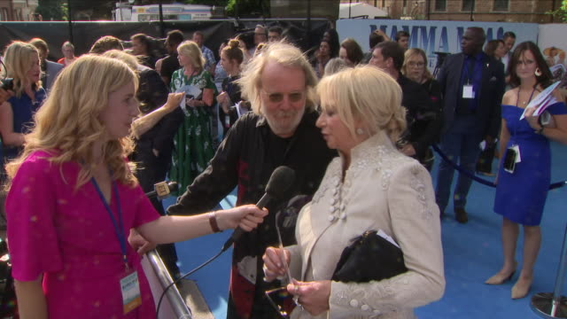 Shows exterior shots press talking to Benny Andersson and Judy Craymer at the 'blue' carpet British Premiere of the film sequel Mamma Mia Here We Go...