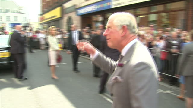 Shows exterior shots Prince Charles and Camilla Duchess of Cornwall outside Yellow Door Patisserie in Portadown on a walkabout shaking hands with...