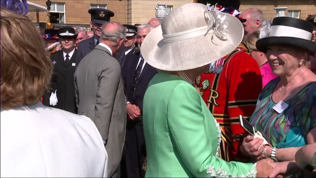 Shows exterior shots Prince Charles Prince of Wales and Camilla Duchess of Cornwall talking to guests at an official Buckingham Palace Summer Garden...