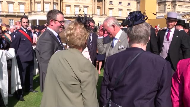 Shows exterior shots Prince Charles Prince of Wales talking to guests and joking about chickens at an official Buckingham Palace Summer Garden Party...
