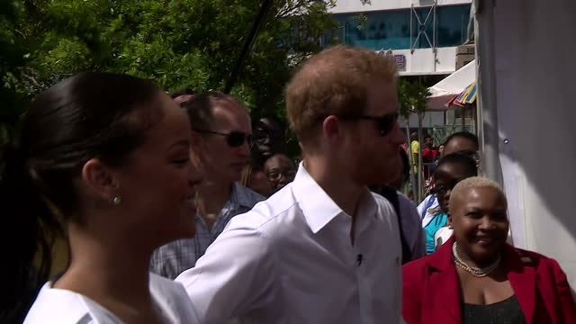 Shows exterior shots Prince Harry and Barbadian Superstar Rihanna talking to barbers about HIV and joking with them at 'Man Aware' event Singer...