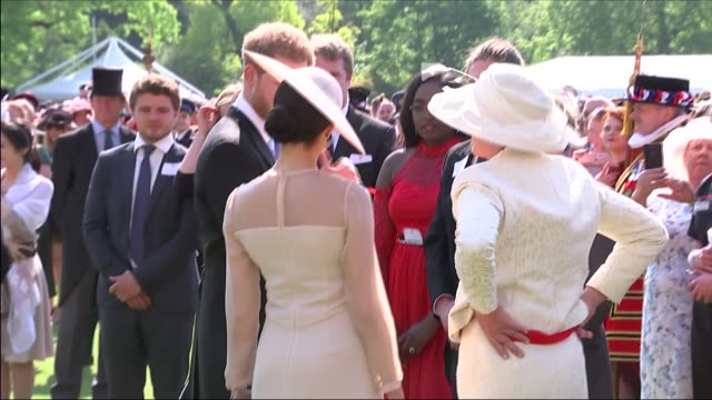 shows exterior shots prince harry duke of sussex and meghan duchess of sussex talking to guests at an official buckingham palace summer garden party... - バッキンガム宮殿点の映像素材/bロール