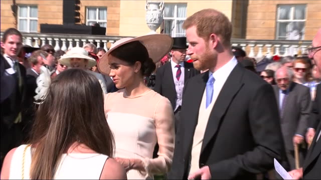 shows exterior shots prince harry duke of sussex and meghan duchess of sussex talking to guests at an official buckingham palace summer garden party... - チャールズ皇太子点の映像素材/bロール