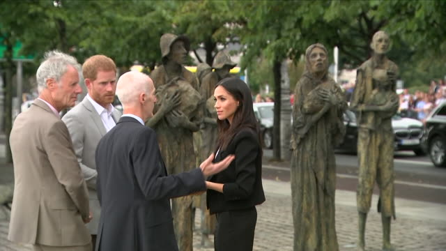 Shows exterior shots Prince Harry Duke of Sussex and Meghan Duchess of Sussex visiting the Famine Memorial at Custom House Quay the memorial...