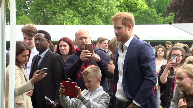 Shows exterior shots Prince Harry shaking hands with performers and watching performance with children at Garden Party The Duke and Duchess of...