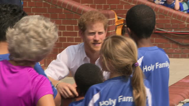 Shows exterior shots Prince Harry talking to children and looking at prize cup at Headingley Stadium during visit to Sky Try Rugby Festival on 6th...