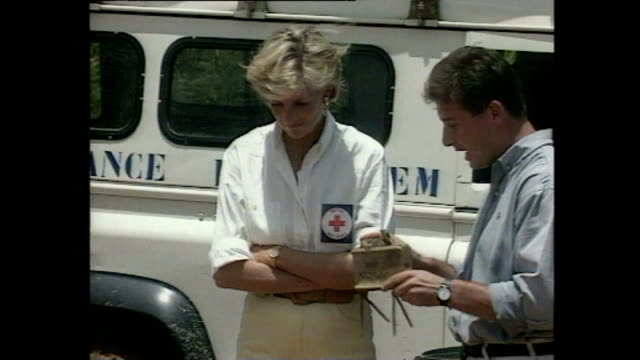 shows exterior shots princess diana being shown deactivated landmines by charity workers and close up of diana holding a hand grenade on trip to a... - 赤十字社点の映像素材/bロール