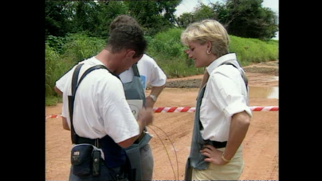 shows exterior shots princess diana laughing with charity workers as they prepare a detonator and pressing button to detonate landmine in cordoned... - 起爆装置点の映像素材/bロール
