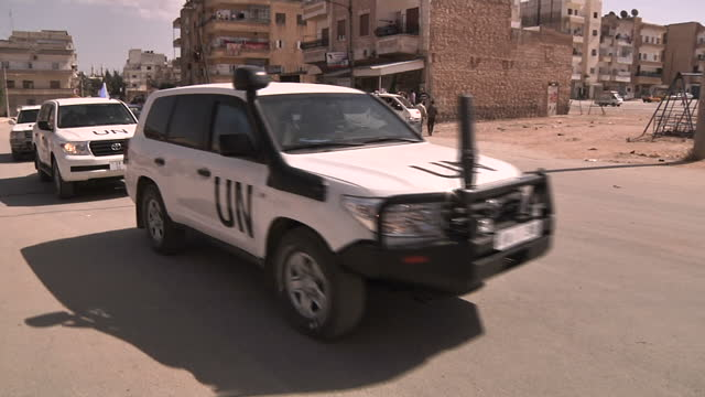Shows exterior shots pro Assad militia in the street police car UN convoy leaving the scene on April 27 2012 in Idlib Syria