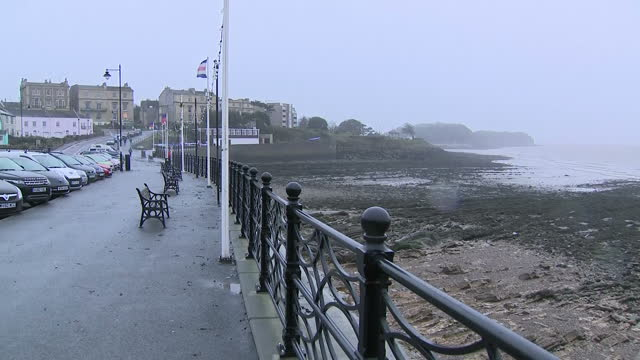 Shows exterior shots promenade with headland in bay and rough looking sea and flags blowing in wind as Storm Eleanor approaches West Coast of England...