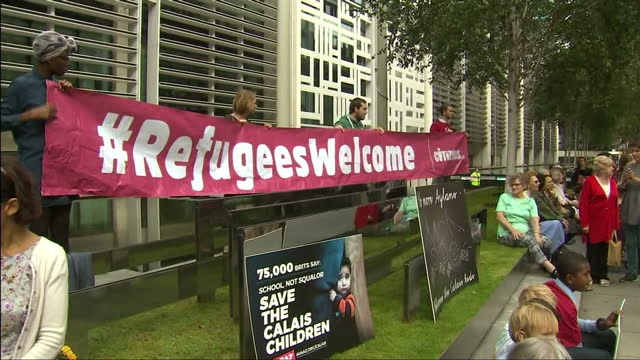 shows exterior shots protest outside the home office in the uk with placards and banners reading save the calais children and no more aylans and... - save the children stock videos & royalty-free footage