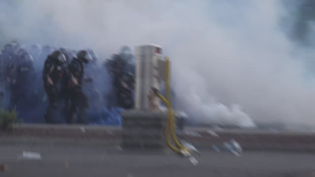shows exterior shots protesters and film crews moving away from smoke from tear gas canisters as riot police advance through clouds of smoke, near... - confrontation stock videos & royalty-free footage