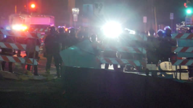 shows exterior shots protesters gathered lighting barricades on fire and armed riot police at scene in streets in minneapolis over death of george... - minnesota stock-videos und b-roll-filmmaterial