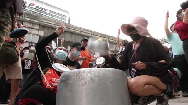 shows exterior shots protesters wearing facemasks due to coronavirus pandemic, gathered outside shopping centre in bangkok banging pots and making... - ミャンマー点の映像素材/bロール