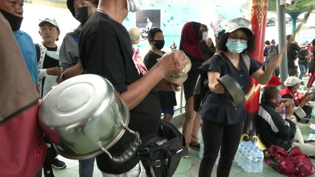shows exterior shots protesters wearing facemasks due to coronavirus pandemic, gathered outside shopping centre in bangkok banging pots and making... - noise stock videos & royalty-free footage