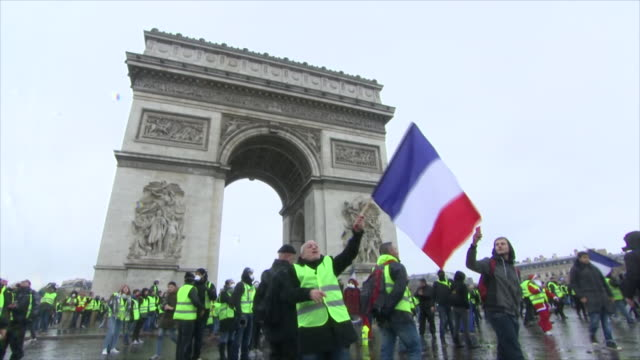 Shows exterior shots protesters wearing yellow vests gathered around the Arc de Triomphe in Paris tear gas being fired amongst them and some digging...