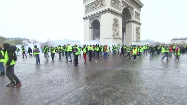Shows exterior shots protesters wearing yellow vests gathered near the Arc de Triomphe in Paris shouting as tear gas is fired in amongst them Dozens...