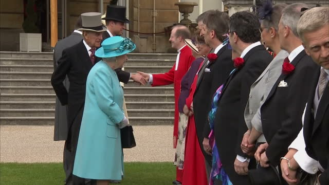 shows exterior shots queen elizabeth ii and prince philip duke of edinburgh shaking hands and talking to guests in receiving line at garden party at... - the queen stock videos and b-roll footage