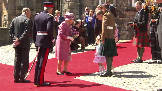 Shows exterior shots Queen Elizabeth II arriving at Stirling Castle and receiving small bunch of flowers from little girl The Queen and Prince Philip...