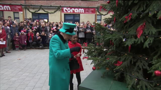 shows exterior shots queen elizabeth ii being presented with ornament and helping shylah gordon to attach it to christmas tree before listening to... - queen royal person stock videos & royalty-free footage