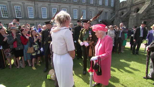 shows exterior shots queen elizabeth ii meeting jason byers and his mother pam byers with his guide dog becky at a garden party at the palace of... - raw footage stock videos & royalty-free footage