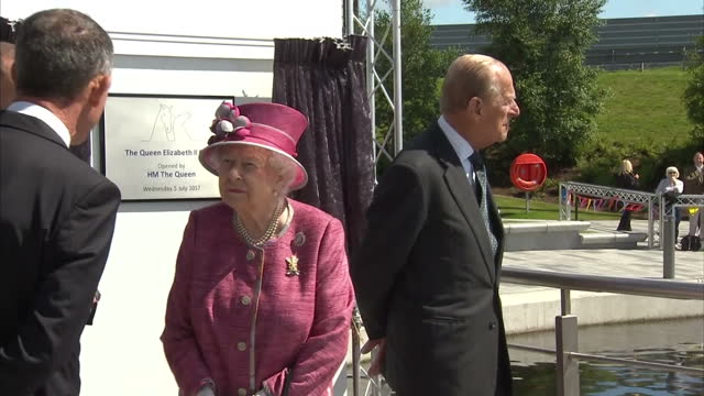 Shows exterior shots Queen Elizabeth II talking to officials as Prince Philip stands in background looking around The Queen opens a new section of...