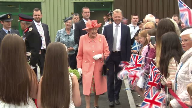 Shows exterior shots Queen Elizabeth II walking out of factory past waiting members of the public holding Union Jack flags and receiving posies of...