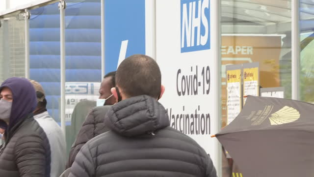 shows exterior shots queue of people, most wearing face masks, standing in the rain outside the mass vaccination centre at heathrow airport, london,... - building exterior stock videos & royalty-free footage