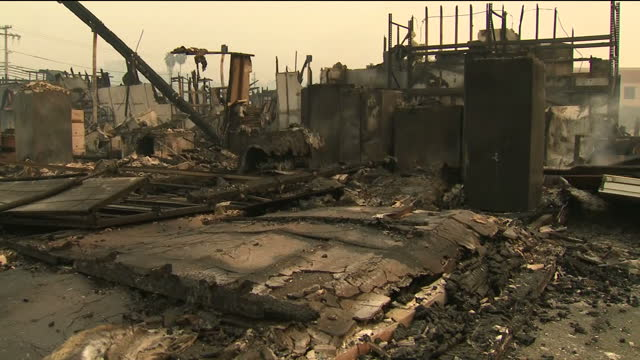 Shows exterior shots remains of buildings destroyed by wildfires with blackened beams rising from debris and piles of black ash across the floor on...