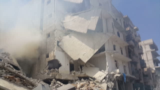 CLEAN Shows exterior shots rescuers clambering over rubble of destroyed building following barrel bomb attack with pan up collapsed floors of...