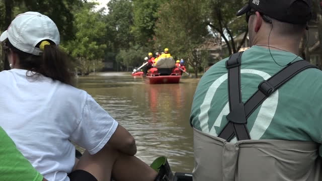 shows exterior shots residents using boats to navigate through flooded streetts in residential neighbourhood with rescuers using inflatable boats to... - soccorritore video stock e b–roll
