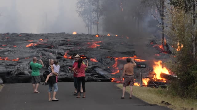 shows exterior shots residents watching and filming as lava spreading across road, swallowing up trees and flames bursting from it in neighbourhood... - hawaii islands stock videos & royalty-free footage
