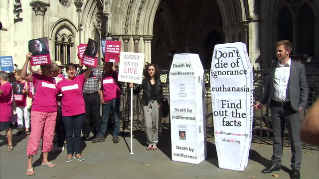 shows exterior shots right to die campaigners outside the royal courts of justice holding signs and chanting we're with noel with antieuthanasia... - euthanasia stock videos & royalty-free footage