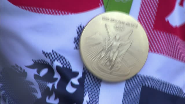 shows exterior shots rio 2016 olympic k1 gold medallist joe clarke walking onto stage waving and smiling and close up shots of his gold medal on... - gold medal stock videos & royalty-free footage