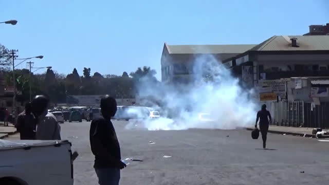 shows exterior shots riot police and protesters on the streets of harare including shots of fires protesters throwing projectiles and police water... - unemployment stock videos and b-roll footage