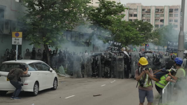 shows exterior shots riot police firing tear gas towards protesters, who try to stop the canisters releasing gas by pouring on water, and riot polcie... - tear gas stock videos & royalty-free footage