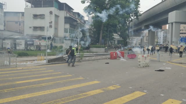 shows exterior shots riot police firing tear gas towards protesters and protesters throwing the canisters back towards the police as smoke begins to... - bombola video stock e b–roll