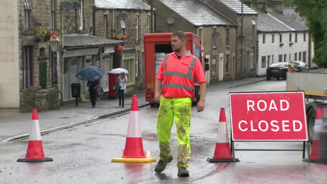 stockvideo's en b-roll-footage met shows exterior shots road block signifying evacuation area inwhaley bridge following damage to dam at toddbrook reservoir and police officers... - bord weg afgesloten