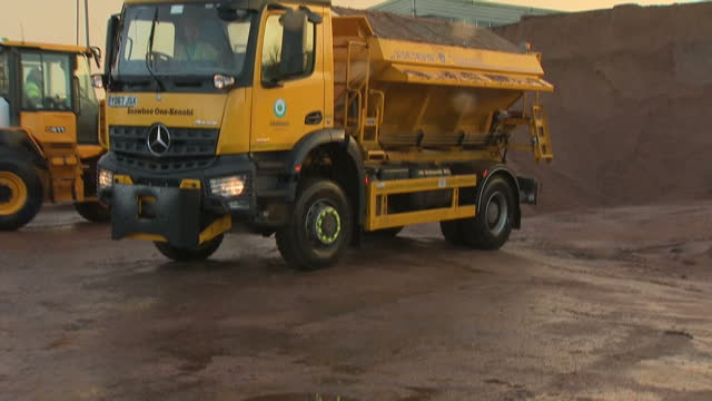 Shows exterior shots road gritting lorry arriving at depot getting filled with salt and sand mixture to treat the roads against ice and close up of...