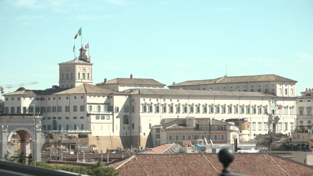 shows exterior shots rooftops of central rome with flags flying frmo the presidential palace quirinal palace. europe's worst affected country, italy,... - democrazia video stock e b–roll