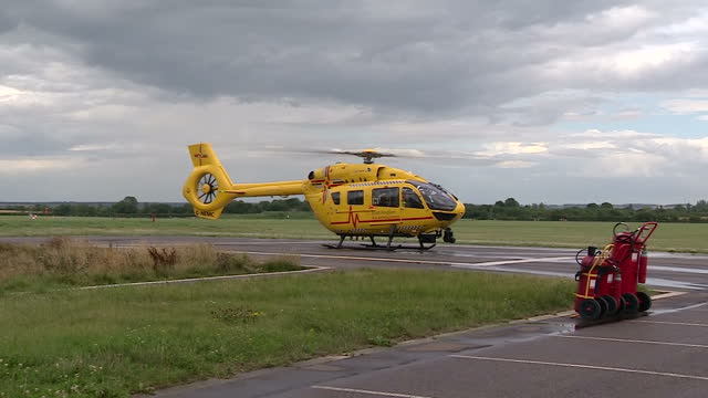 Shows exterior shots rotor blades slowing after yellow air ambulance helicopter from the East Anglian Air Ambulance Service lands on runway on 27th...