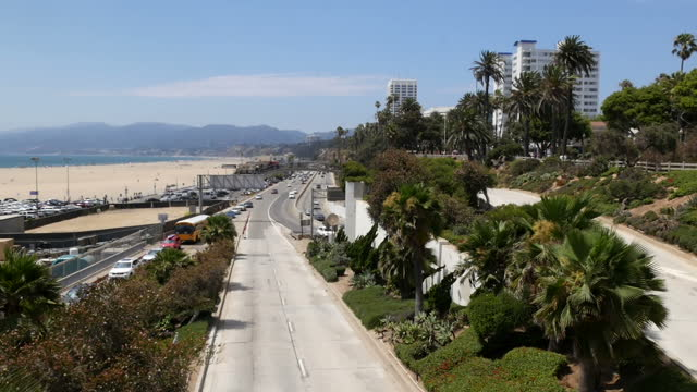 Shows exterior shots Santa Monica beachfront with cars driving along Pacific Coast Highway and buildings on hillside above on 26th July 2017 in Santa...