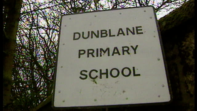 shows exterior shots sign for dunblane primary school and police officers outside the school press and photographers gathered in road worried parents... - råmaterial bildbanksvideor och videomaterial från bakom kulisserna