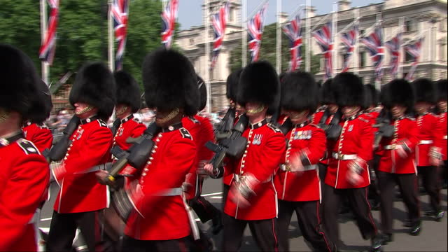 shows exterior shots soldiers in the coldstream guards marching past houses of parliament at state opening of parliament the queen's speech was... - the queen's speech state opening of uk parliament stock-videos und b-roll-filmmaterial