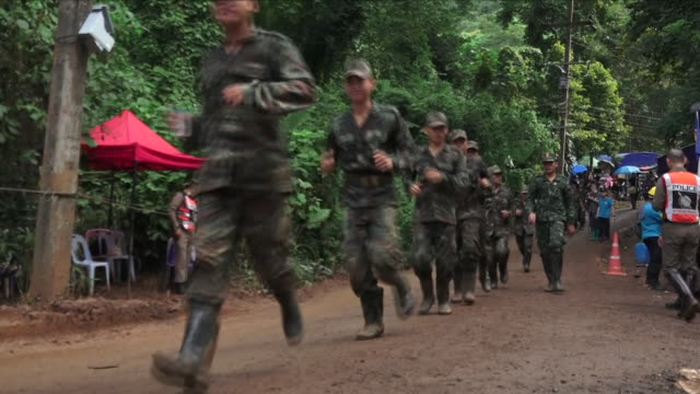 Shows exterior shots soldiers jogging through camp The death of an experienced diver inside the cave where 12 boys and their football coach are...