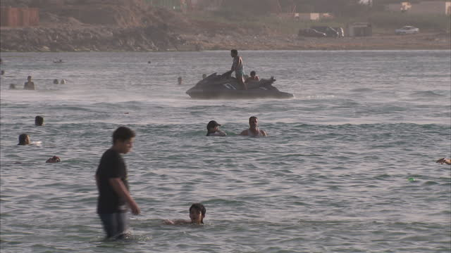shows exterior shots someone on jet ski out at sea people walking along a busy beach on june 06 2015 in tripoli libya - acquascooter video stock e b–roll
