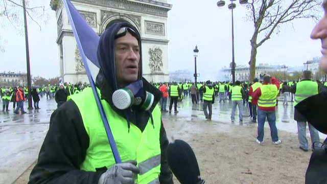 vídeos de stock, filmes e b-roll de shows exterior shots soundbite from yellow vest protester speaking on reason for protesting opinion on europe and president macron dozens of people... - vest
